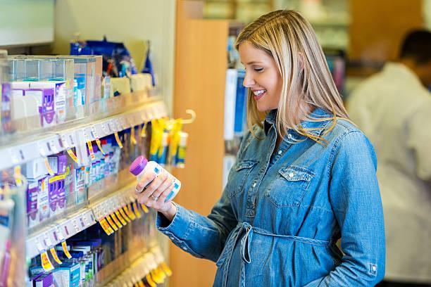 schwangere mutter liest pränatale vitamin-label in apotheke - lieblingsrezepte stock-fotos und bilder