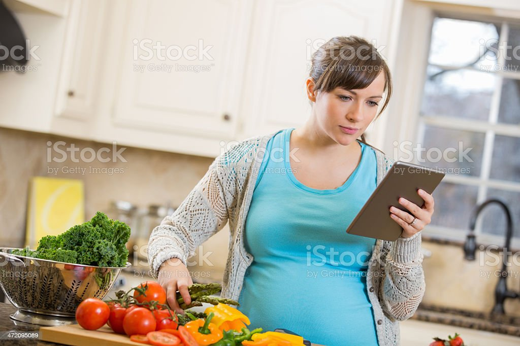 Pregnant mother reading recipe on digital tablet while cooking royalty-free stock photo