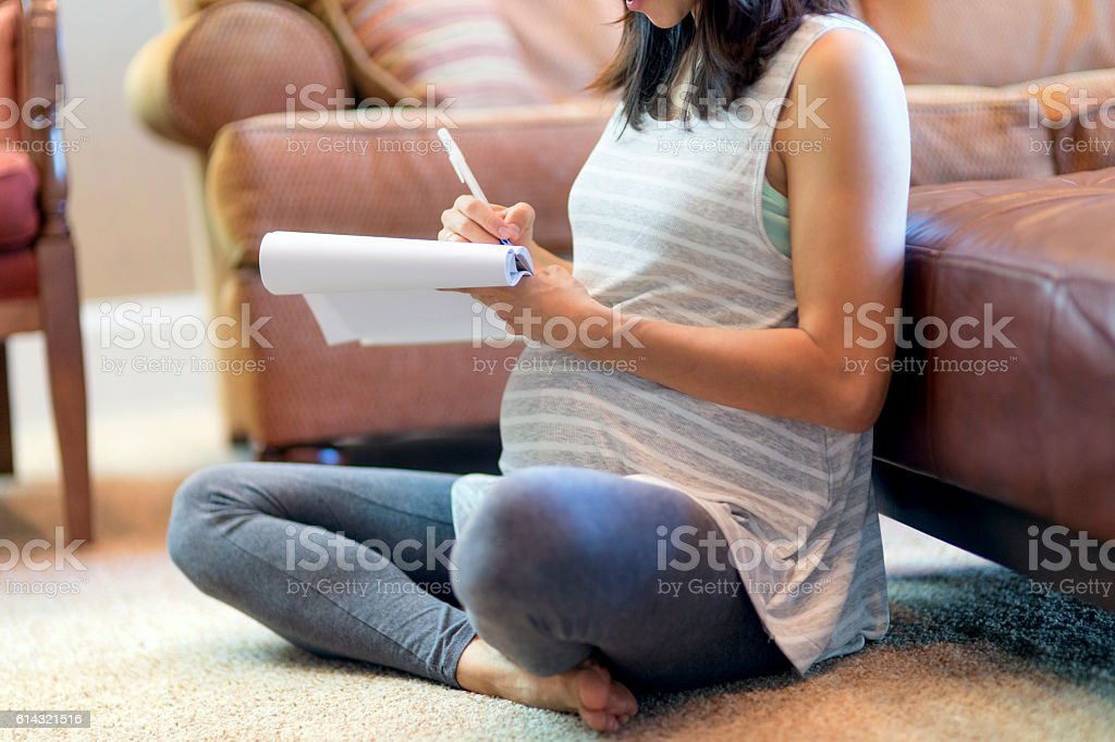 Pregnant mother sitting on carpet using a pad and paper – Foto