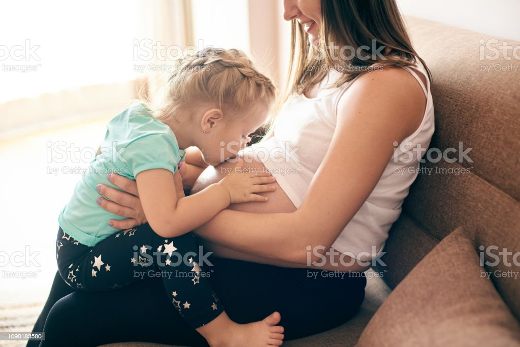 Pregnant mother sitting with cute daugher kissing big belly stock photo