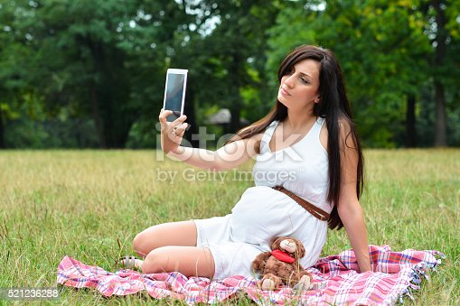 istock Pregnant Mother with A Teddy Bear and Taking Selfie 521236288