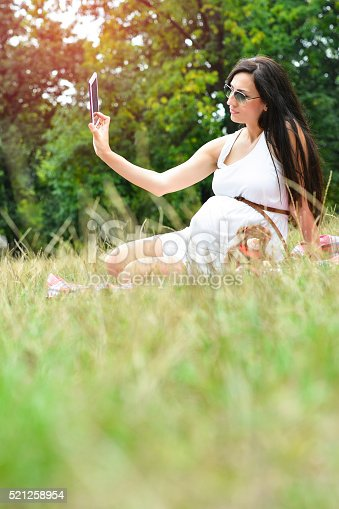 istock Pregnant Mother with A Teddy Bear and Taking Selfie 521258954