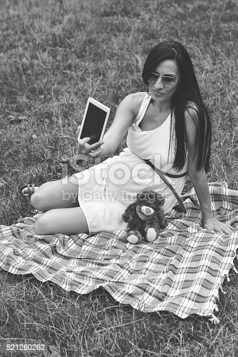 istock Pregnant Mother with A Teddy Bear and Taking Selfie 521260262