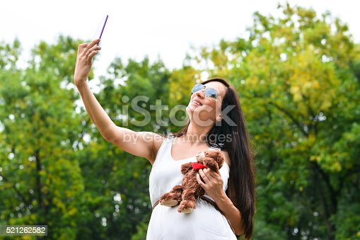 istock Pregnant Mother with A Teddy Bear and Taking Selfie 521262582