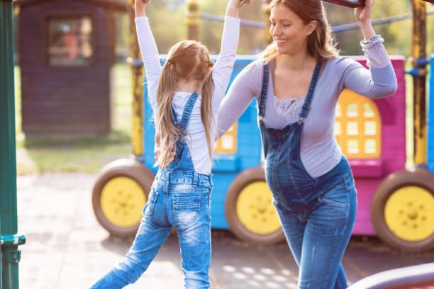 schwangere mutter mit ihrer tochter, mit freude spielen auf dem spielplatz - latzhose für schwangere stock-fotos und bilder