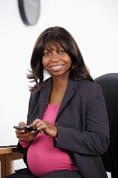 Schwangere Büroangestellter mit einem Smartphone – Foto