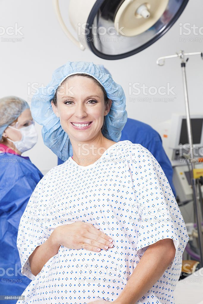 Pregnant patient preparing for cesarean section in operating room stock photo