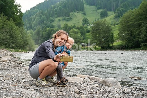 Beautiful pregnant woman with braided long hair takes a selfie on her smartphone with little son at the mountains river