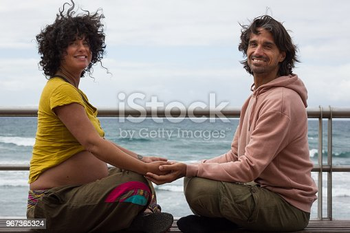 istock Pregnant woman and future father enyoing leisure time by the sea 967365324