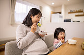 Pregnant woman and her daughter eating fruit in dining room
