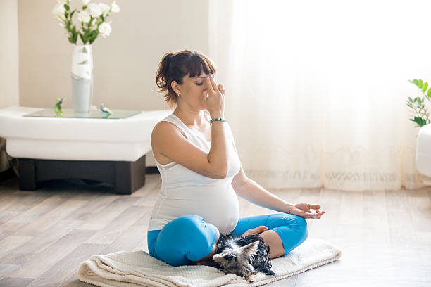 Pregnant woman and her pet dog relaxing with yoga home - foto de stock