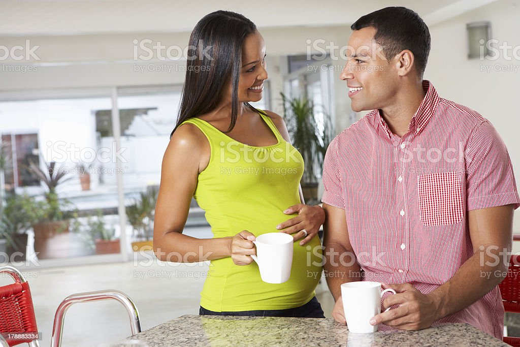 Pregnant Woman And Husband Having Breakfast In Kitchen royalty-free stock photo