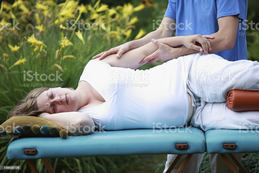Pregnant woman arm massage by physical therapist stock photo