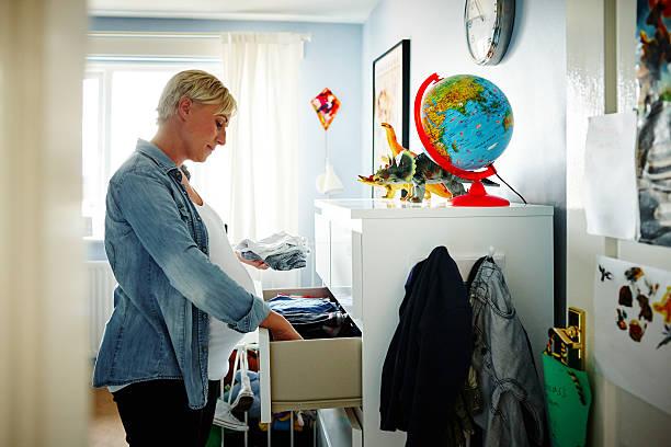 Pregnant woman arranging the wardrobe stock photo