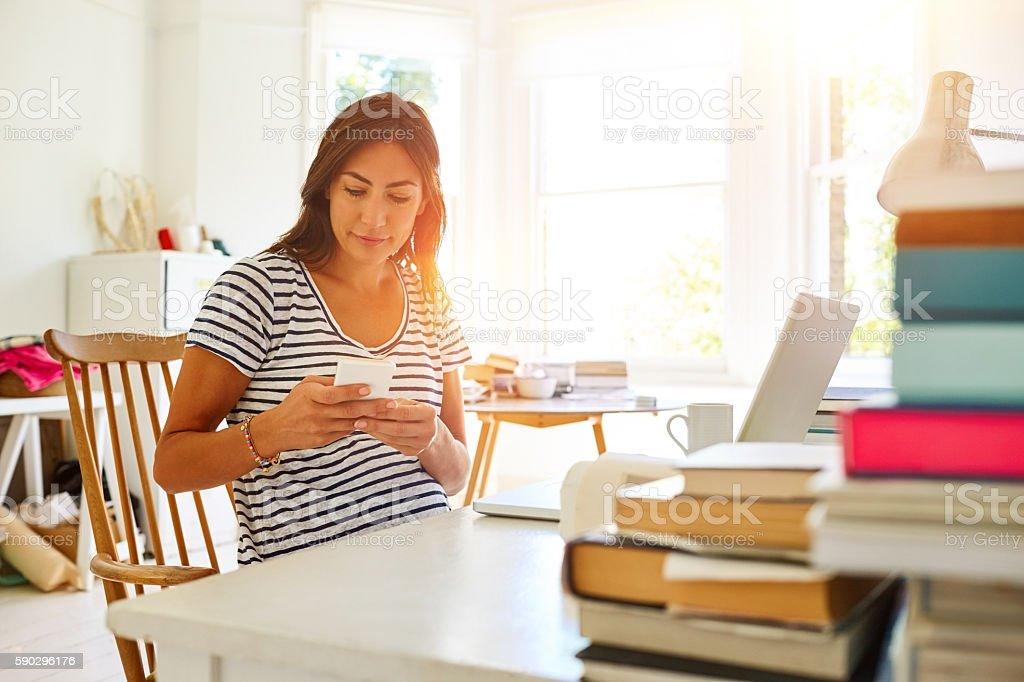 Pregnant woman at home office using mobile phone Стоковые фото Стоковая фотография