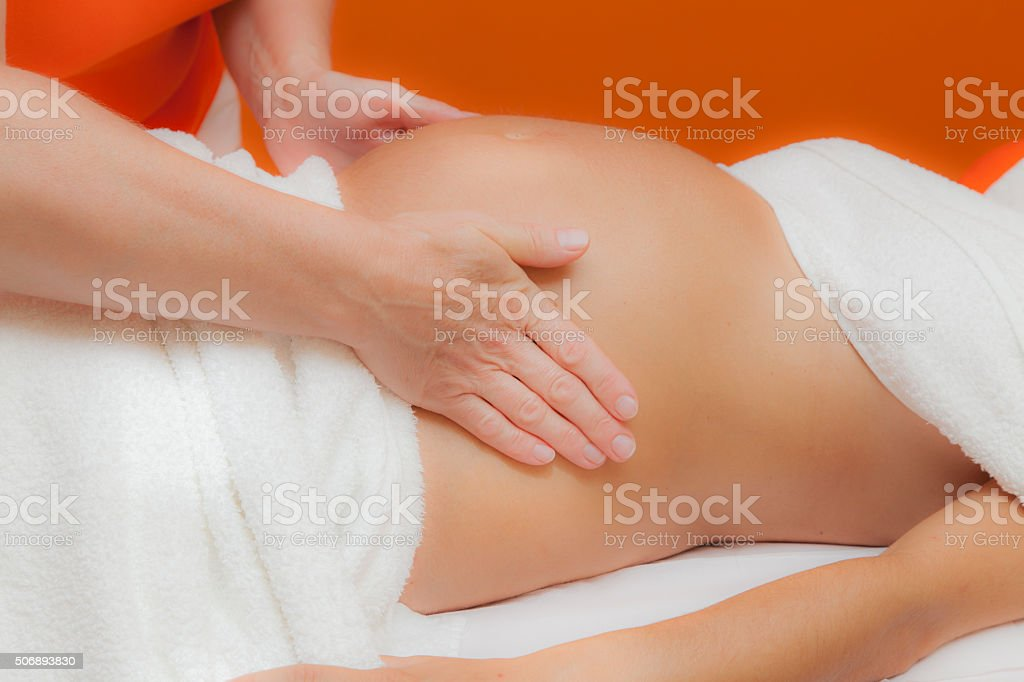 Pregnant woman at prenatal massage, glamour clarity effect stock photo