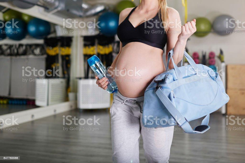 Zwangere vrouw op de sportschool holding sport tas en bidon foto