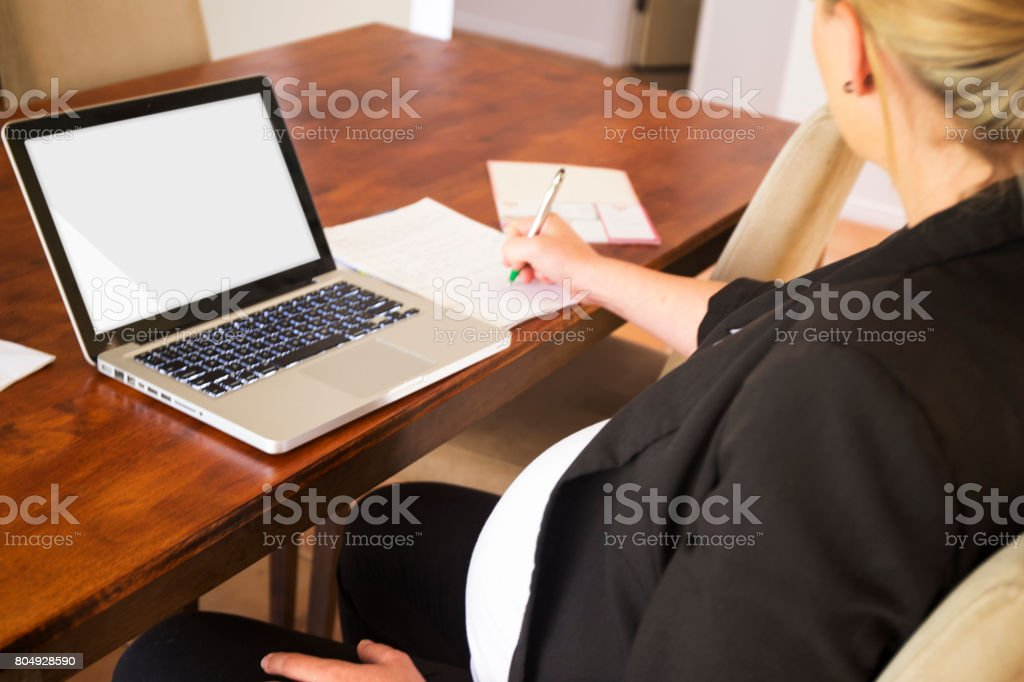 Pregnant woman at work stock photo