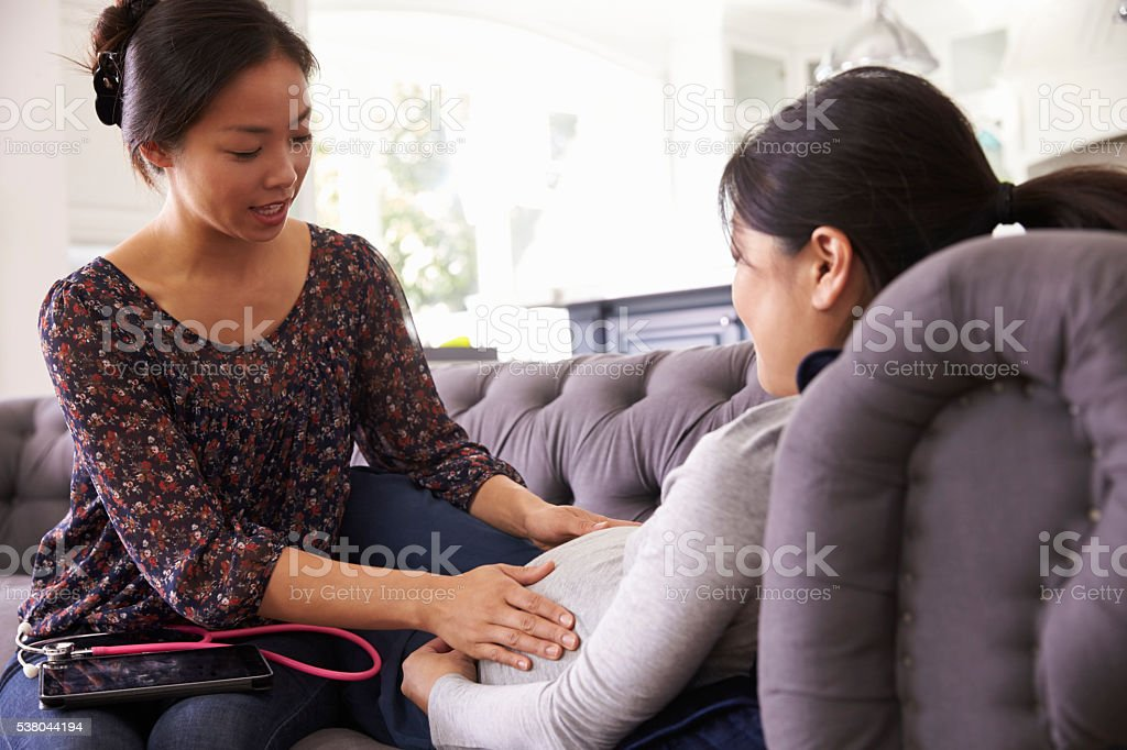 Pregnant Woman Being Examined At Home By Midwife stock photo