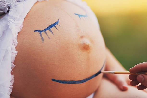 pregnant woman belly closeup with smile funny face - makeup for pregnant women stock photos and pictures