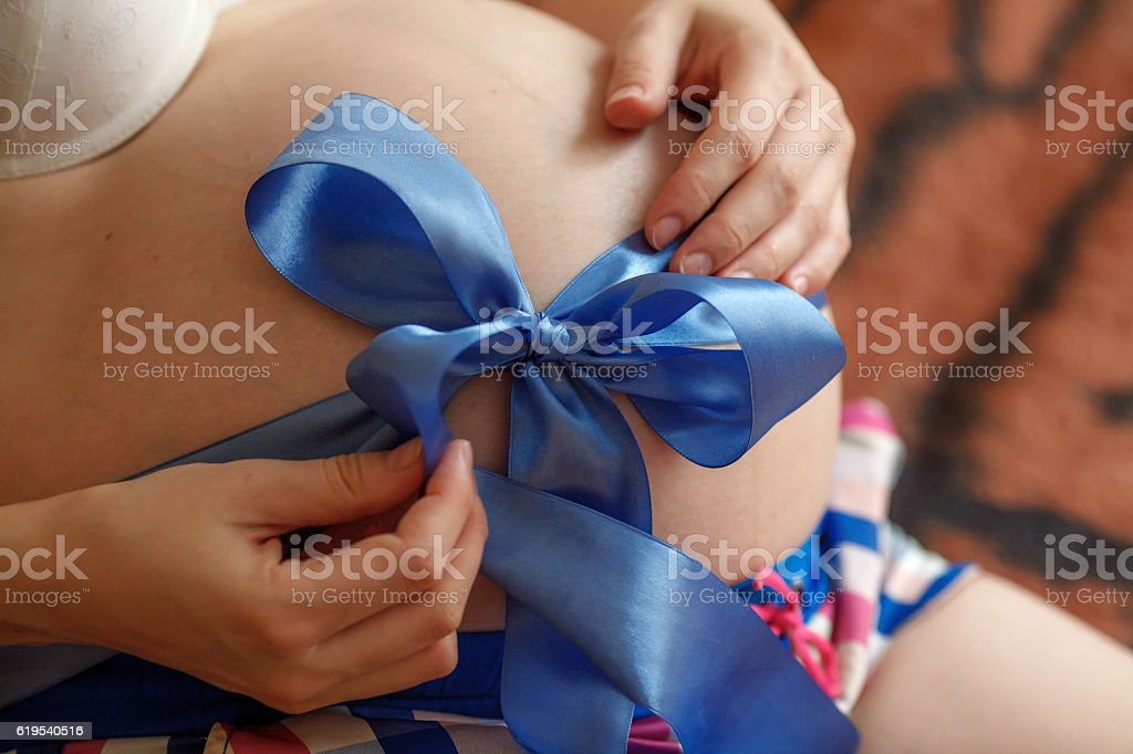 Pregnant woman. Belly with blue ribbon. Third trimester of pregnancy stock photo
