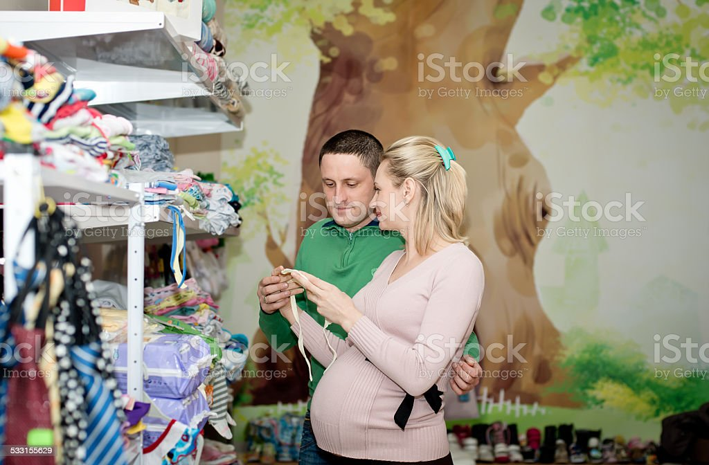 Pregnant woman buying baby clothes in supermarket stock photo