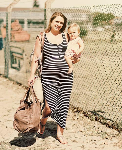 schwangere frau, die für kleinkinder über schlechte umgebung, ein deprimierter und erschöpft - kleinkind busy bags stock-fotos und bilder
