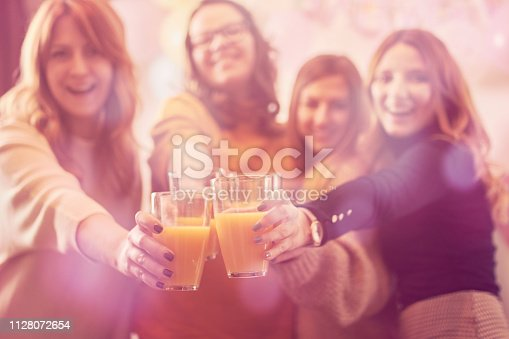 609058672 istock photo Pregnant woman celebrating baby shower party with friends. Focus on glass. 1128072654
