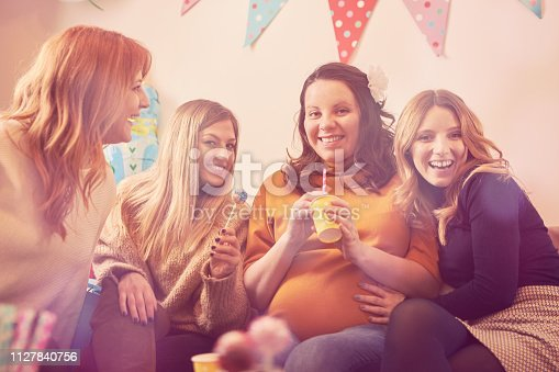 609058672 istock photo Pregnant woman celebrating baby shower party with friends. 1127840756