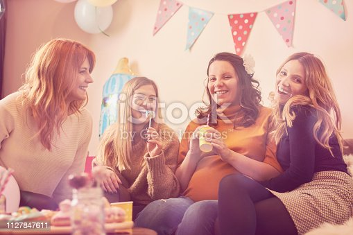 609058672 istock photo Pregnant woman celebrating baby shower party with friends. 1127847611