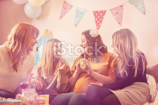 609058672 istock photo Pregnant woman celebrating baby shower party with friends. 1128965944