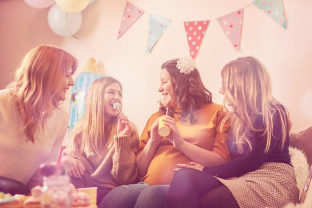 Pregnant woman celebrating baby shower party with friends. stock photo