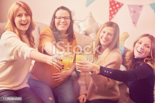 istock Pregnant woman celebrating baby shower party with friends. 1129384593