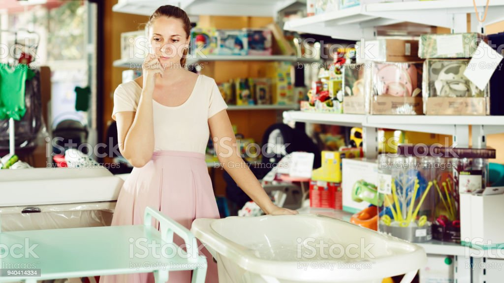 pregnant woman choosing between baby bath and changing table in shop stock photo