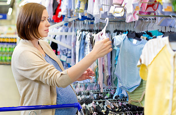 pregnant woman choosing newborn clothes at baby shop stock photo