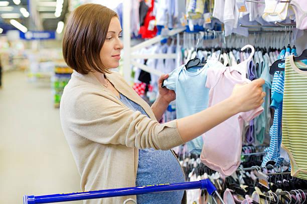 pregnant woman choosing newborn clothes at baby shop – Foto