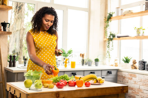 Pregnant woman choosing vegetables for her salad. stock photo