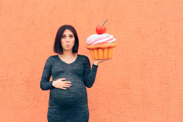 Schwangere Frau Craving Süßigkeiten halten riesige Cupcake – Foto