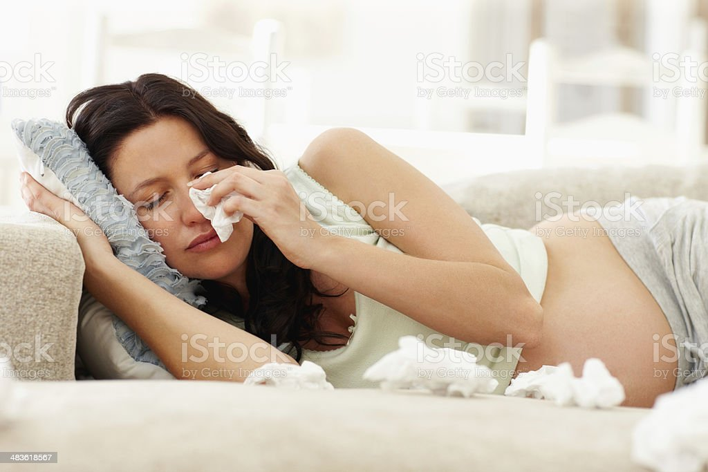 Pregnant woman crying on couch stock photo