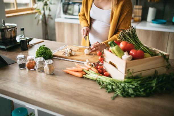 Schwangere Frau schneidet Pilze ab – Foto