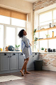 Beginning of the day. Pregnant woman smiling and dancing in her kitchen in the morning.