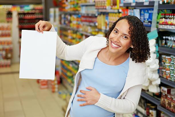 schwangere frau zeigt leere blatt in super-markt - sprüche zur schwangerschaft stock-fotos und bilder