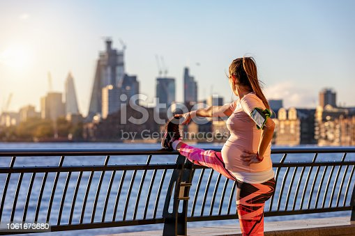 Pregnant woman does her stretching after workout in front of the skyline of London