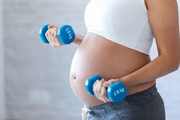 Schwangere Frau macht Übung mit Hanteln zu Hause. – Foto