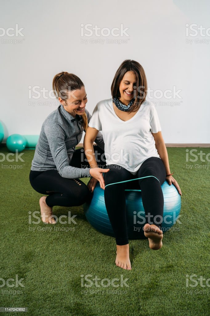 Pregnant woman doing fitness ball and pilates exercise with coach....