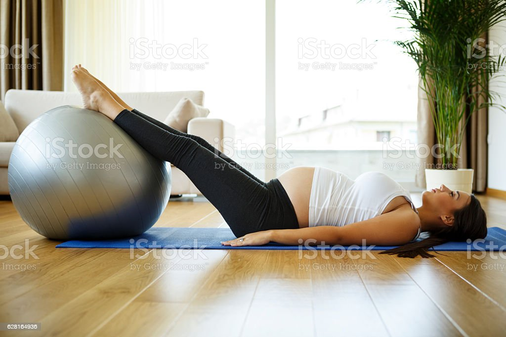Pregnant woman doing pilates exercises stock photo