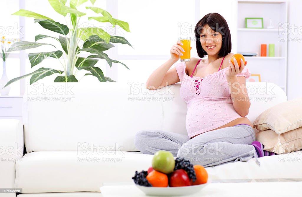 Pregnant woman drinking fruit juice and holding orange royalty-free stock photo