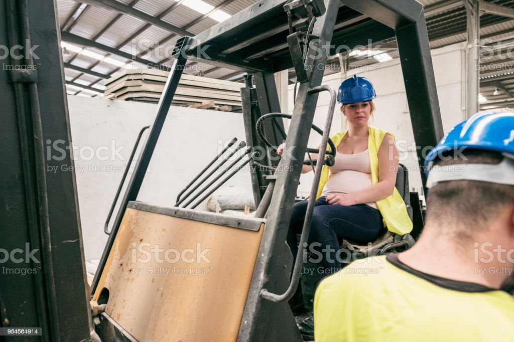 Pregnant woman driving forklift in concrete factory while looking worker stock photo