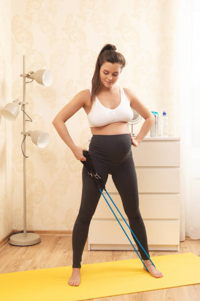 pregnant woman during her fitness workout at home - resilience concept stock photos and pictures