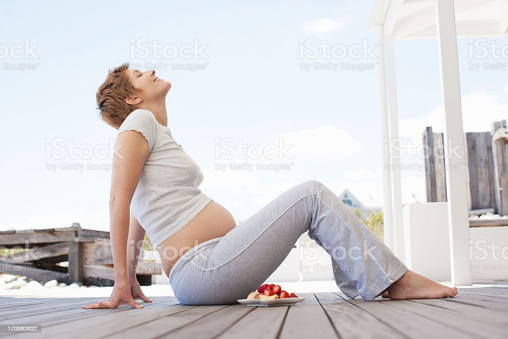 Pregnant woman eating fruit on deck royalty-free stock photo